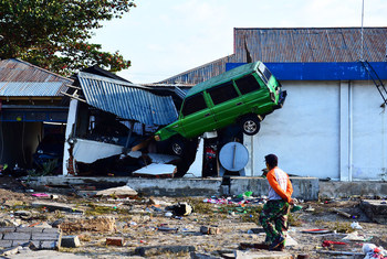 A man walks past a car hanging on the roof of a house in the aftermath of the tsunami which struck after an earthquake hit Palu, Central Sulawesi, Indonesia. (29 September 2018)