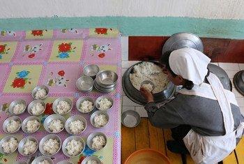 Trabalhadora humanitária prepara refeição para crianças financiada pelo PMA em Hwanghae Sul, na Coreia do Norte.