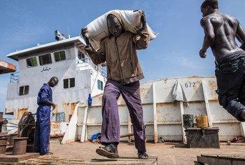 إمدادات غذائية يقدمها برنامج الأغذية العالمي يتم تفريغها من بارجة نهرية  في بلدة ملكال ، جنوب السودان. ملف (أغسطس 2018)