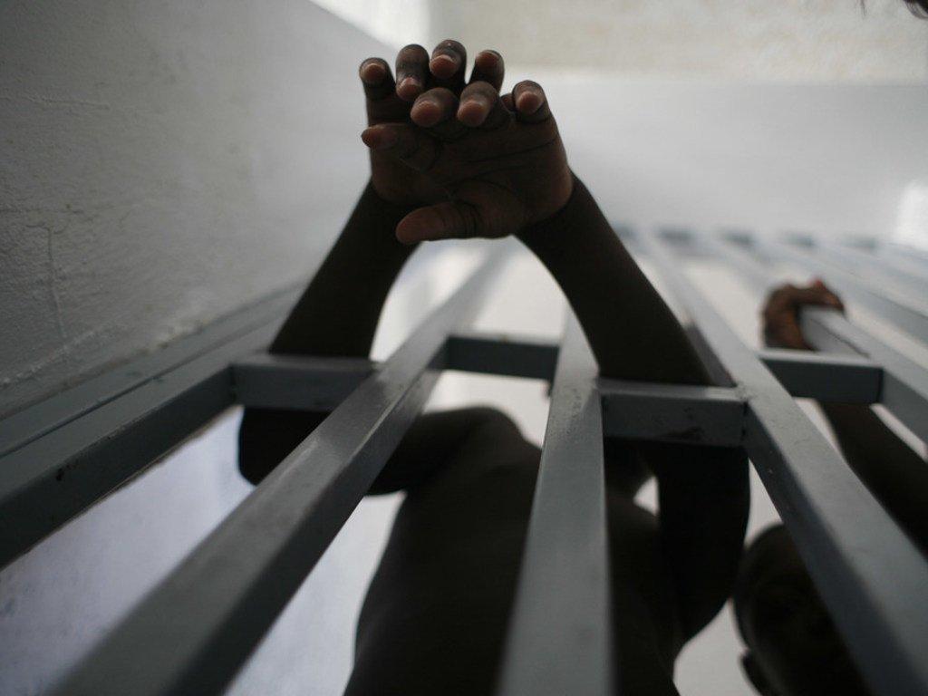 [ARCHIVO] Joven prisionero saca sus manos a través de los barrotes de una cárcel