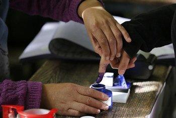 Dans un bureau de vote à Kaboul, une femme plonge son doigt dans une encre indélébile après avoir voté (archive)