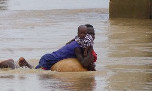 A mother and child attempt to escape the flood water in Niger State, Nigeria, following torrential rains which have hit the region since mid-July 2018. (file October 2018).