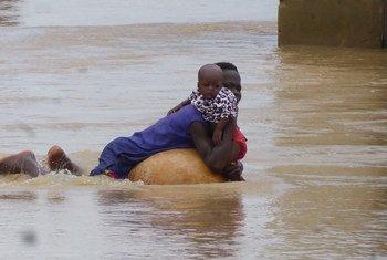 Mãe e criança tentam escapar das cheias no estado de Niger, na Nigéria.