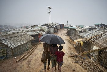 Rohingya refugees make their way down a footpath during a heavy monsoon downpour in Kutupalong refugee settlement, Cox's Bazar district. 2018.