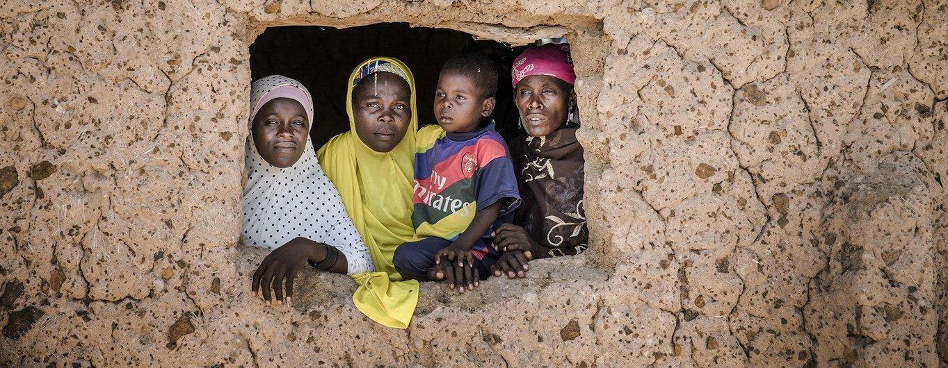 أفراد عائلة نيجرية ينظرون من خلال نافذة منزلهم في قرية دراقو في إقليم مرادي في النيجر.
