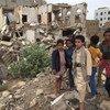 Vijana wa kiume wakiwa wamesimama katika jengo lililobomolewa sehemu za Saada Yemen.