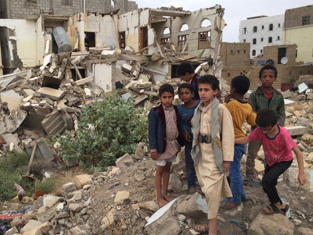 也门萨达的男孩站在被武装团体轰炸的建筑物前。