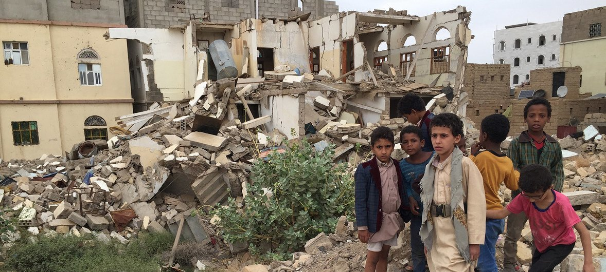 Young boys standing in front of damaged buildings in Saada, Yemen, where bombing has left many neighbourhoods in the city  strewn with wreckage and debris following ground fighting between armed groups.