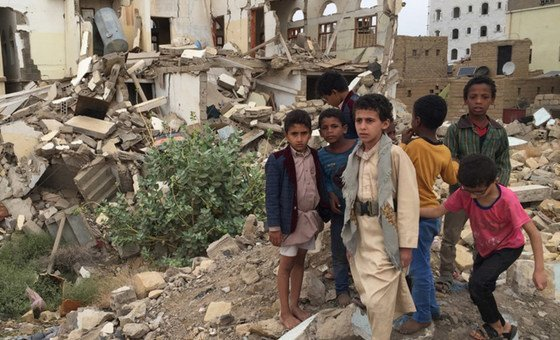 Young boys standing in front of damaged buildings in Saada, Yemen, where bombing has left many neighbourhoods in the city are strewn with wreckage and debris following ground fighting between armed groups.