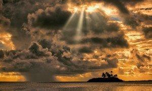 O nascer do sol e uma nuvem de chuva reunem-se no atol de Laamu, Maldivas.