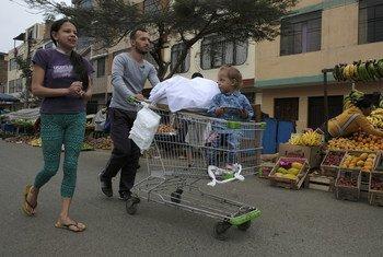 Kelvis Briceño, 27, su mujer Mareli, 26, y su hija Ximena, de dos años, en Lima Perú. Llegaron de Perú hace un año desde Venezuela y venden dulces en la calle para pagar el tratamiento de diálisis de Mareli.