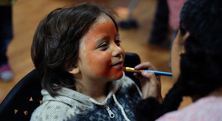 Una voluntaria pinta la cara a una niña venezolana en el centro deportivo Iñaquito, en Quito, Ecuador, que cuenta con el apoyo de ACNUR.