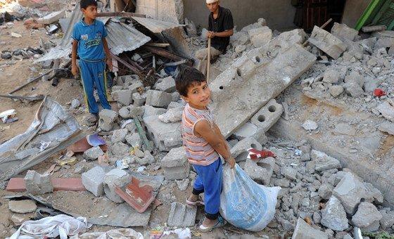 Палестинские дети разбирают завалы в поисках домашней утвари.