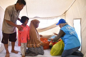 An UNHCR employee helps a family of survivors of the earthquake in Central Sulawesi move into a UNHCR emergency family tent, in the Wani Village of the Indonesian island of Sulawesi. 25 October 2018.