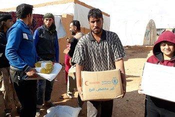 موظفو برنامج الأغذية العالمي يقومون بتوزيع 6690 حصة غذائية كافية لأكثر من 33 ألف شخص اليوم 5 تشرين الثاني 2018 بالقرب من مخيم الركبان شرق سوريا.