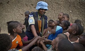 A Rwandan peacekeeper from the UN Multidimensional Integrated Stabilization Mission in Mali (MINUSMA) Formed Police Unit (FPU) speaks with children while patrolling the streets of Gao in northern Mali.