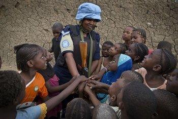 إحدى أفراد حفظة السلام الروانديين، من وحدة الشرطة المشكلة في بعثة الأمم المتحدة في مالي، مع الأطفال أثناء قيامها بدوريات في شوارع غاو في شمال مالي.