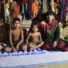 A Rohingya refugee from Myanmar, sits with two out of her four children in their shelter at Nayapara camp, south-east Bangladesh.