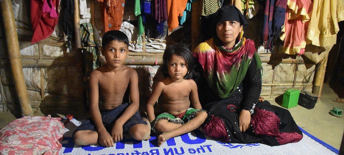 Mkimbizi wa Rohingya kutoka Myanamr, akiwa ameketi na watoto wake wawili kati ya wanne katika malazi yao kwenye kambi ya Nayapara Kusini Mashariki mwa Bangladesh 22 Oktoba 2018.