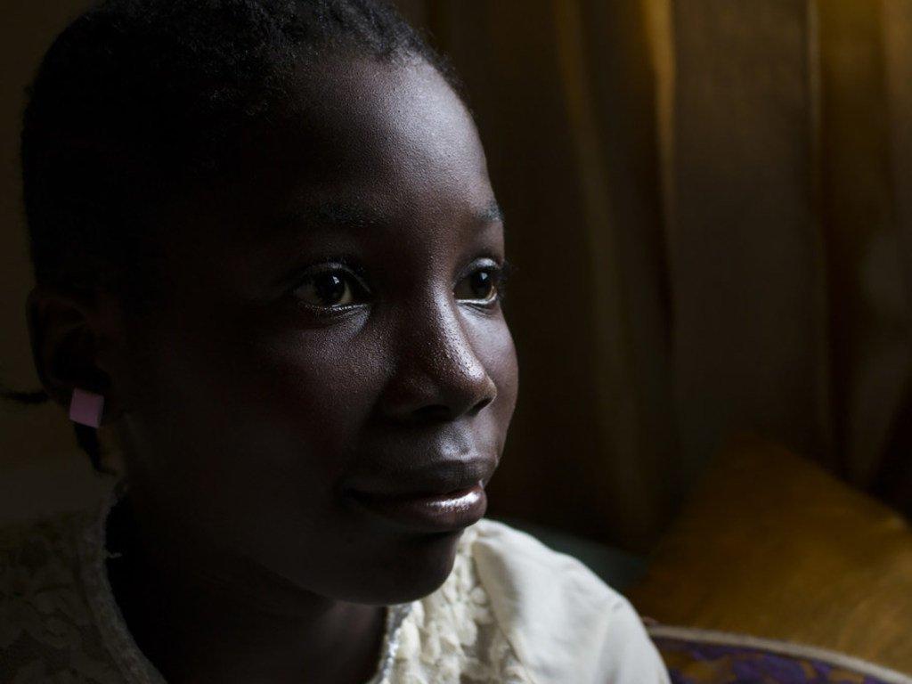 12岁的斯特拉坐在床上。她和两个兄弟姐妹与母亲睡在一张床上。 斯特拉出生在尼日利亚,但她的出生从未被登记过。 她现在居住在利比里亚,在她的尼日利亚籍父亲去世后,她无法证明自己与这两个国家的关系。