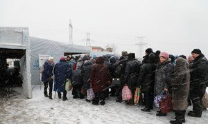 People wait in line at Maiorske Entry/Exit Checkpoint in eastern Ukraine