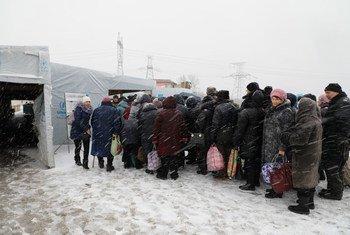 Des gens font la queue au point de passage de Maiorske, dans l'est de l'Ukraine.