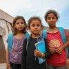 Junaina, nord d'Idlib, en Syrie : dans ce camp de fortune, des filles portant des sacs à dos de l'UNICEF se tiennent devant leur école. Abritée sous une tente, l'école accueille 350 enfants âgés de 7 à 14 ans.