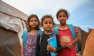 فتيات سوريات يرتدين حقائب ظهر بشعار اليونسف خارج مدرسة مشيدة من الخيام، في مخيم جونايا المؤقت في ريف إدلب الشمالي، حيث يتعلم 350 طفلا من سن 7 إلى 14 عاما.