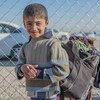 الطفل مصطفى يحمل حقيبته المملوءة بأشيائه الخاصة في مخيم الخازر للنازحين في محافظة نينوى.