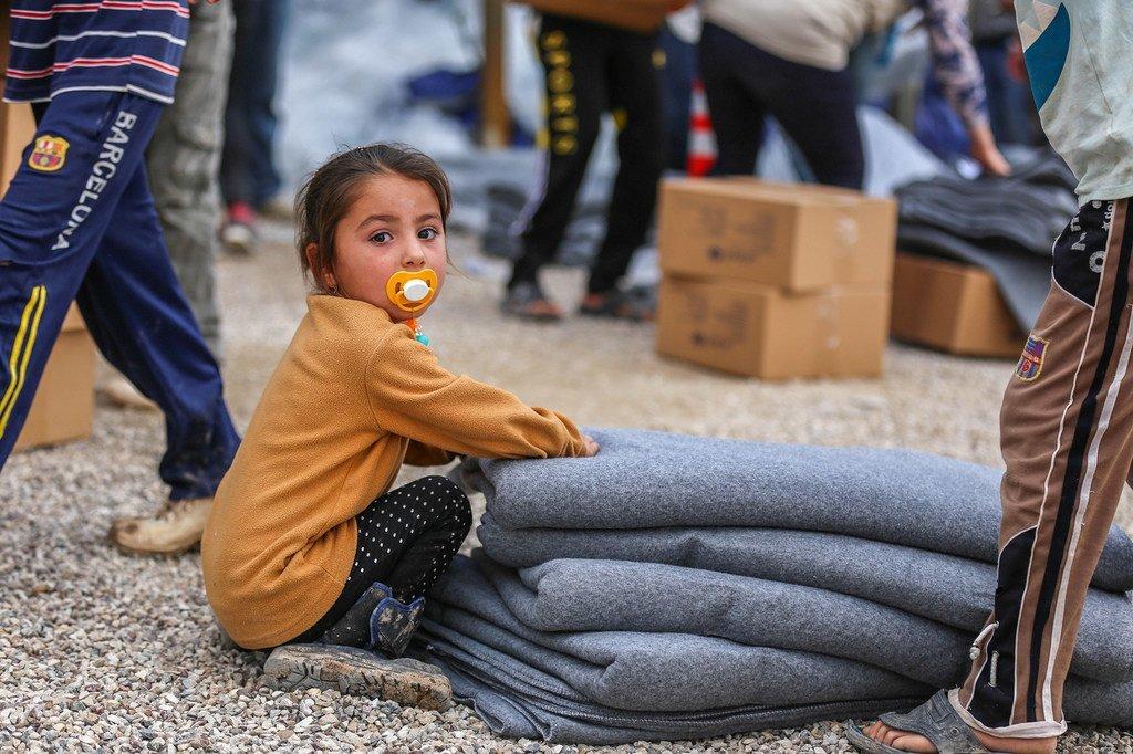 طفلة تجلس بجانب الإعانات التي تم استلامها للوقاية من البرد القارس في الشتاء داخل مخيمات دهوك.
