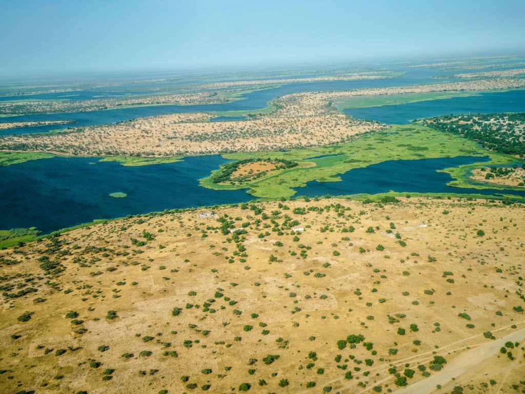 Aerial view over Lake Chad from the aeroplane, clearly shows patched of desertification. In the past 50 years, Lake Chad basin shrank from 25,000 square kilometers to 2,000 square kilometers.