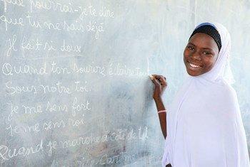 在乍得湖区的一处难民营,16岁的阿伊莎正在学校的黑板前。