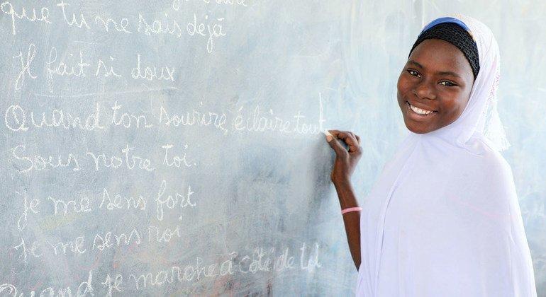 Aisha Mahamadou, de 16 años, escribe en la pizarra de su escuela del campo de refugiados de Dar es Salam en la región del Lago Chad