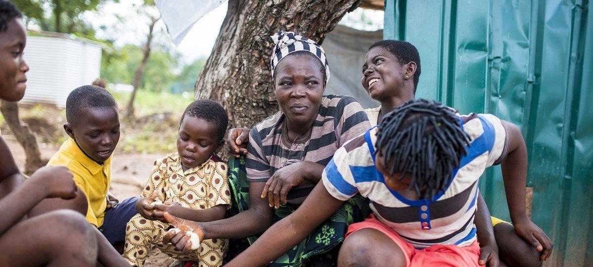 Familia ya wakimbizi kutoka Cameroon ikiwa nje ya kibanda chao katia makazi ya Adagom, kusini mashariki mwa Nigeria.