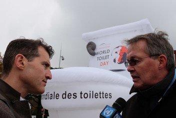 """联合国新闻记者在日内瓦为纪念2018世界厕所日而安放的巨大充气厕所前采访非政府组织""""供水和环境卫生合作理事会""""(Water Supply and Sanitation Collaborative Council )执行主任Rolf Luyendijk。"""