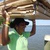 Mulher carrega painéis solares nas Honduras.