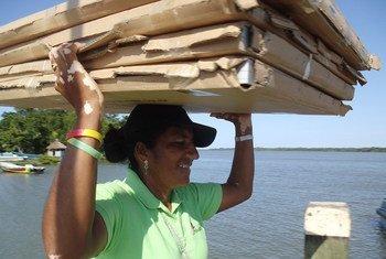 Mujer transportando paneles solares en Honduras.
