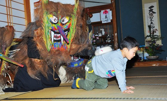A Raiho-shin known as Toshidon places mochi, a rice cake, on the back of a young boy to grant him good luck.