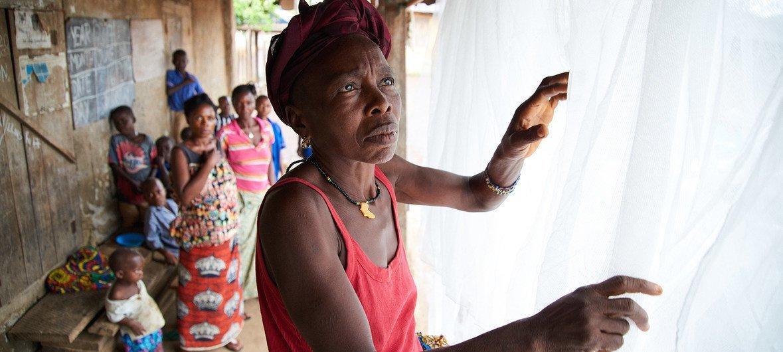 امرأة تعلق ناموسية تسلمتها خلال حملة لتوزيع الناموسيات في منطقة غيما ديما في مقاطة كينيما في سيراليون.