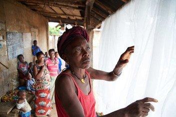 Mwanamke akifunga chandarua cha mbu baada ya kukipokea wakati wa kampeni ya kitaifa ya ugawaji vyandarua vya mbu kwenye kijiji cha Giema Dama Wilaya ya Kenema nchini Sierra Leone , June 2017