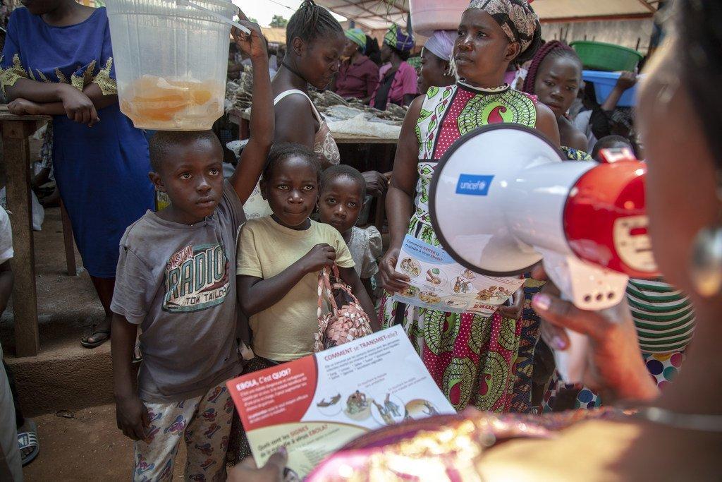 Un membre de l'équipe de sensibilisation de l'UNICEF sur Ebola s'adresse aux enfants dans un marché de Beni, une ville du Nord-Kivu touchée par le virus Ebola, en République démocratique du Congo.