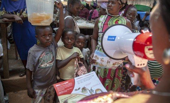 Un membre de l'UNICEF sensibilise des enfants au risque d'Ebola dans un marché de Beni, au Nord-Kivu, en République démocratique du Congo. L'agence onusienne appuie le lancement d'une campagne de vaccination contre la rougeole