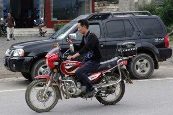 Motociclista usando un teléfono móvil mientras conduce en China.
