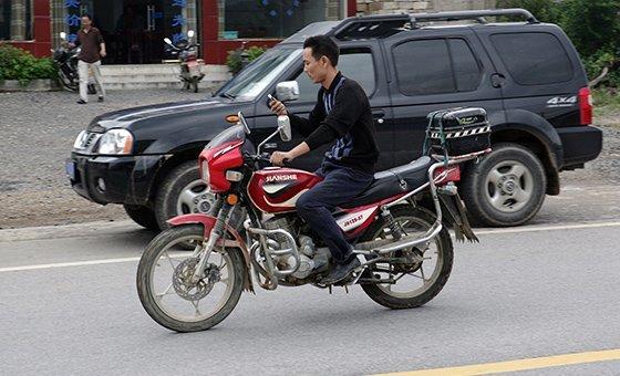 在中国,这个人边骑摩托车边看手机。