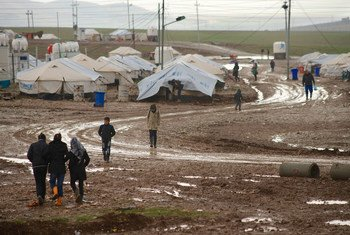In this file photograph, children at a refugee camp in Suleimaniyah, northern Iraq, walk to their school, along a muddy path on a cold, rainy winter day.