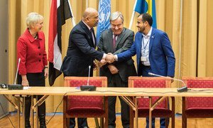 Yemen's foreign minister Khaled al-Yamani (left) and Head of Ansarullah delegation Mohammed Amdusalem (right) shake hands on a ceasefire in and around the Yemeni port of Hudaydah, in the presence of the UN Secretary-General António Guterres (centre) and the host of the meeting, the Swedish Foreign Minister Margot Wallström.