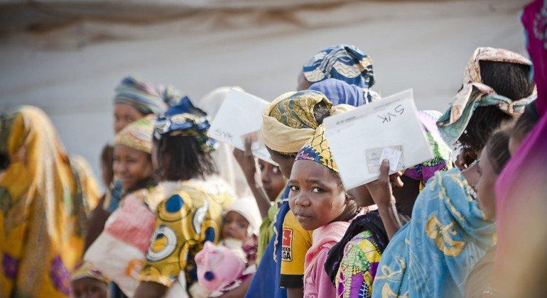 Mujeres y niños centroafricanos hacen fila en un centro de refugiados de Camerún para conseguir comida.