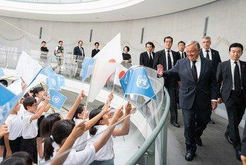 Crianças de escolas japonesas acenam com bandeiras japonesas e das Nações Unidas para receber o secretário-geral António Guterres no Museu da Bomba Atómica de Nagasaki.