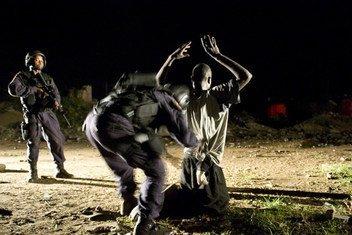 Au milieu de bâtiments abandonnés du centre-ville de Monrovia, une personne suspectée de transporter de la drogue et des armes est fouillé.