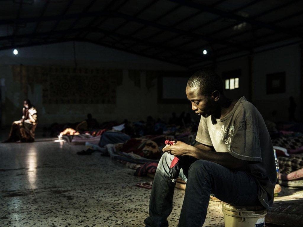 Un migrant est assis près d'une source de lumière entrant par l'une des deux seules fenêtres alors qu'il tente de se réchauffer dans un centre de détention situé en Libye, le 1er février 2017. Lors de la visite de l'UNICEF, 160 hommes y étaient détenus.